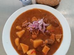 Uherský guláš (vepř.+ hov. maso, brambory, rajčata, paprika), pečivo (sójová bulka)